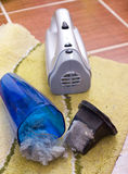 Vacuum cleaner full of dust and hair clots. Close up of open cordless vacuum cleaner full of dust and hair clots on the carpet. Housekeeping concept stock image