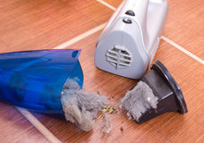 Vacuum cleaner full of dust and hair clots. Close up of open cordless vacuum cleaner full of dust and hair clots on tiled floor. Housekeeping concept royalty free stock images