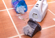 Vacuum cleaner full of dust and hair clots. Close up of open cordless vacuum cleaner full of dust and hair clots on tiled floor. Housekeeping concept stock photography
