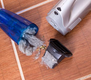 Vacuum cleaner full of dust and hair clots. Close up of open cordless vacuum cleaner full of dust and hair clots on tiled floor. Housekeeping concept royalty free stock photo