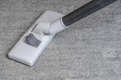 Vacuum cleaner on the gray carpet. Gray black drunk vacuum cleaner on the carpet under the suction angle stock image
