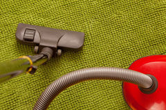 Vacuum cleaner on a green carpet. Royalty Free Stock Image