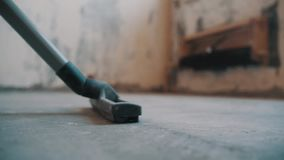 Vacuum cleaner hose nozzle riding over concrete floor at building site. Vacuum cleaner hose black plastic nozzle with brushes riding over concrete floor back and stock footage