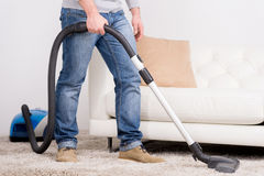 Vacuum Cleaner. A man does house work with a vacuum cleaner Royalty Free Stock Photos