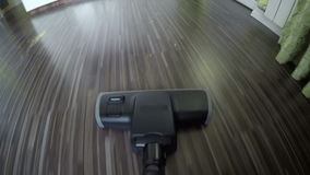 Vacuum cleaner point of view rolling back and forth on a wooden floor. 4K stock footage