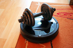 Vacuum cleaner robot and weight Royalty Free Stock Photography