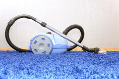 Vacuum cleaner stand  on blue carpet. Royalty Free Stock Images