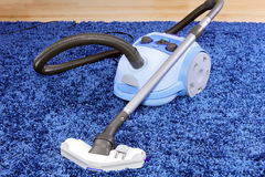Vacuum cleaner stand  on blue carpet. Royalty Free Stock Photos