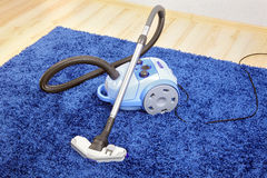Vacuum cleaner stand  on blue carpet. Stock Photos