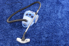 Vacuum cleaner stand  on blue carpet. Royalty Free Stock Photo