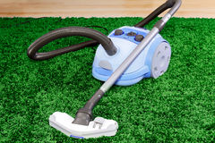 Vacuum cleaner stand  on green Royalty Free Stock Images