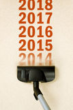 Vacuum Cleaner sweeping year number 2014 from carpet. Vacuum Cleaner sweeping year number 2014 from Brand New Carpet leaving sequence 2015, 2016. e.t.c. Happy Stock Image