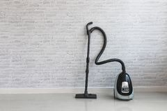 Vacuum cleaner on white concrete background in the house. Stock Photos