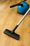 Vacuum cleaner on wooden floor. A blue domestic vacuum cleaner on a wooden floor Royalty Free Stock Image