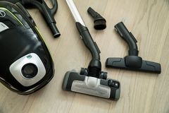 Vacuum cleaner on the wooden floor. Cleaning home stock photo