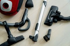 Vacuum cleaner with the right complements on the wooden floor. Cleaning home stock photos