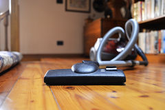Vacuum cleaner and wooden floor. A wooden floor and a vacuum cleaner ready to e used to clean it Royalty Free Stock Photography