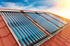 Vacuum collectors- solar water heating system. On red roof of the house stock photo