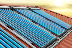 Vacuum collectors- solar water heating system. On red roof of the house under shining sun royalty free stock photography