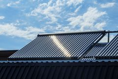 Vacuum solar water heating system on the house roof. royalty free stock images