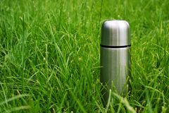 Vacuum insulated steel thermos bottle in the green grass at summer picnic stock photography