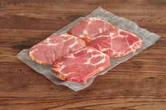 Vacuum packed meat. Displayed on a wooden background Royalty Free Stock Photo