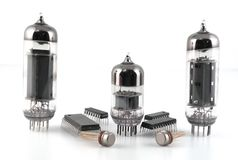 Vacuum radio tubes and semiconductor chips. Over white Stock Images