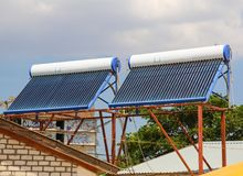 Vacuum solar cells for water heating system on the house roof stock images