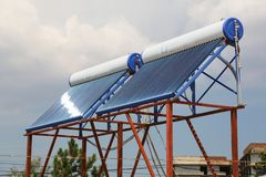 Vacuum solar cells for water heating system on the house roof.  royalty free stock photography