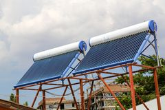 Vacuum solar cells for water heating system on the house roof.  stock photo