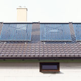 Vacuum solar water heating system on a house roof. Royalty Free Stock Image