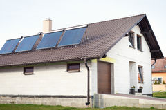 Vacuum solar water heating system on a house roof. Power and energy concept royalty free stock image