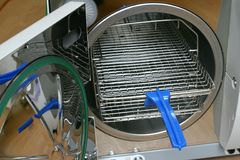 Vacuum steriliser chamber with rack removal tool. Vacuum steriliser chamber with safe plastic rack removal tool. Removal tool is neccessary due to high stock image