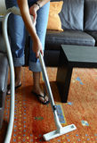 Vacuuming a carpet. Woman cleaning a carpet with central vacuum cleaner Royalty Free Stock Images