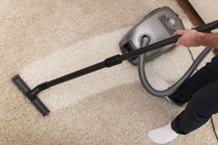 Vacuuming a carpet Royalty Free Stock Image