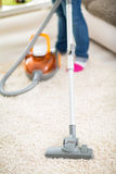 Vacuuming carpet with vacuum cleaner Royalty Free Stock Image