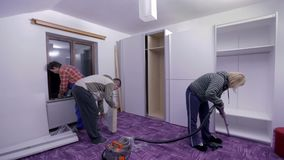 Vacuuming, checking wardrobe and opening new packages. Two men are assembling new furniture in freshly painted room. They use compact cordless drill-driver stock footage