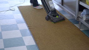 Vacuuming clean a floor in a business stock video footage