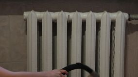 Vacuuming between sections of a radiator. The woman carries out cleaning between sections of a radiator of heating by means of the vacuum cleaner stock video footage