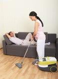 Vacuuming woman and resting man Royalty Free Stock Photography