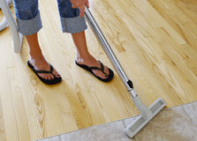 Vacuuming wood floor. Woman cleaning hardwood and tile floor with central vacuum cleaner Royalty Free Stock Photo