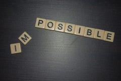 Vad är möjlig? Inte omöjligt Bokstavstegelplattor ställde upp på svart bakgrund med borttagna bokstäver arkivfoton