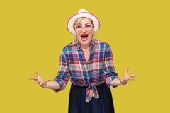 Vad önskar du från mig? Stående av den ilskna moderna stilfulla mogna kvinnan i tillfällig stil med hatt- och glasögonanseende so royaltyfri fotografi