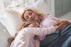 Vad drömmer de omkring? Moder och dotter som håller ögon c royaltyfri fotografi