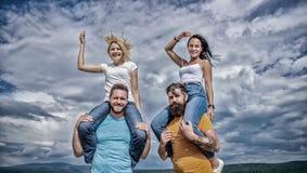 Vad vi skulle kalla gyckel Lyckliga m?n som piggybacking deras flickv?nner F?r?lskat le f?r sk?mtsamma par p? molnig himmel ?lska royaltyfri foto