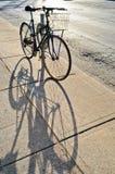 Vada in bicicletta bloccato allo scaffale ed alla sua ombra Immagini Stock Libere da Diritti
