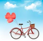 Vada in bicicletta con i palloni a forma di cuore rosso davanti ad un cielo blu Immagini Stock