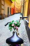 Vada in bicicletta con il mazzo di fiori sulla barra della maniglia Fotografie Stock Libere da Diritti