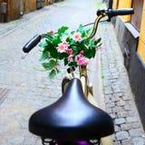 Vada in bicicletta con il mazzo di fiori sulla barra della maniglia Fotografia Stock Libera da Diritti
