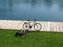 Vada in bicicletta ed uomo di rilassamento sull'erba vicino ad uno stagno Immagine Stock Libera da Diritti